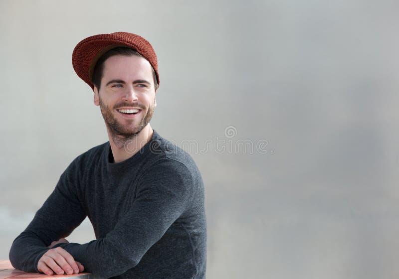 Koele kerel met hoed die in openlucht glimlachen royalty-vrije stock afbeeldingen