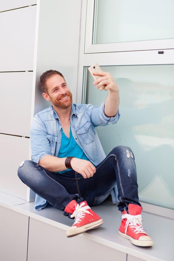 Koele kerel met mobiel tijdens zijn rust in het bureau royalty-vrije stock fotografie