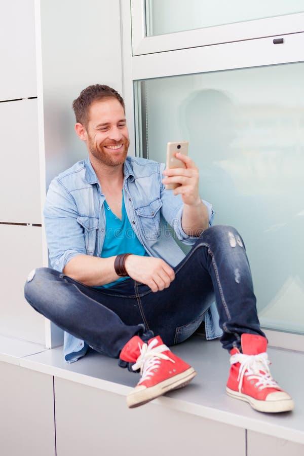 Koele kerel met mobiel tijdens zijn rust in het bureau stock foto's