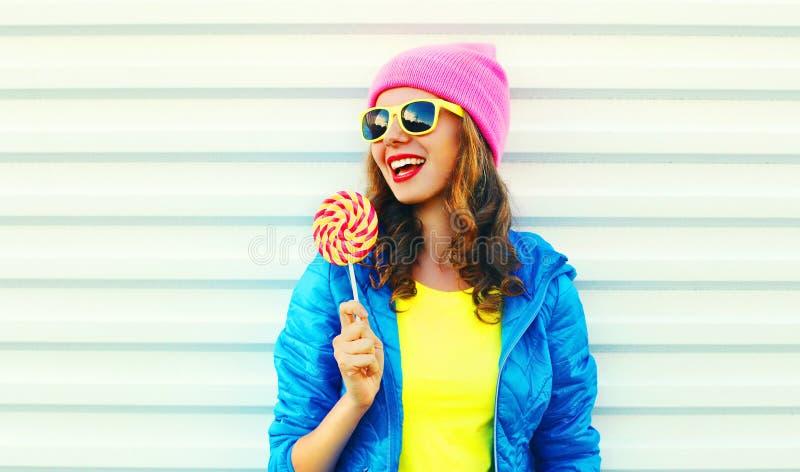 Koele lachende vrouw van de portretmanier de vrij met lolly in kleurrijke kleren over witte achtergrond die een roze hoed dragen stock foto