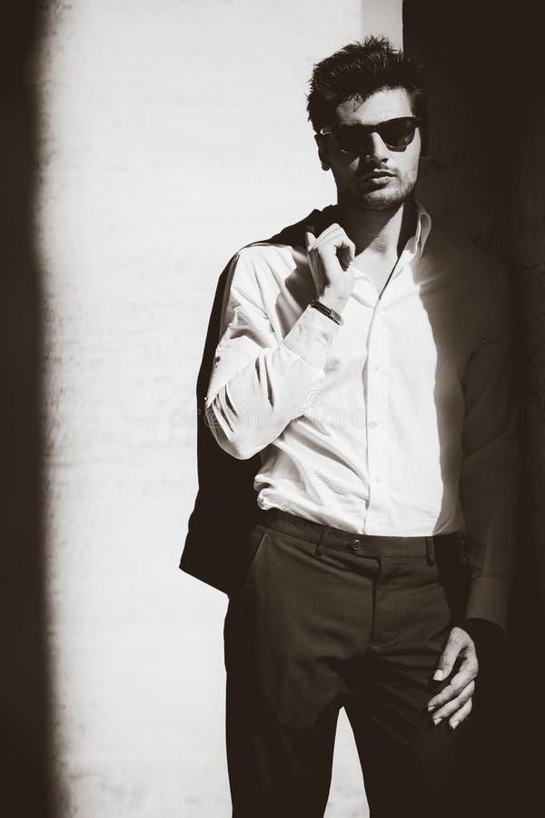 Koele mens met zonnebril en wit overhemd in schemering royalty-vrije stock afbeeldingen