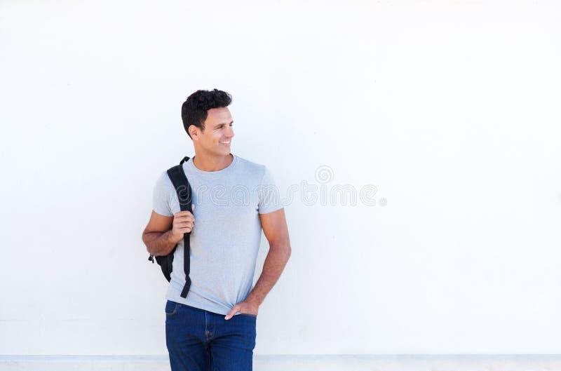 Koele oudere kerel die met zak tegen witte achtergrond glimlachen royalty-vrije stock fotografie