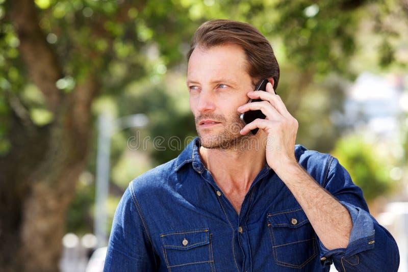 Koele oudere mens die op mobiele telefoon spreken stock foto's