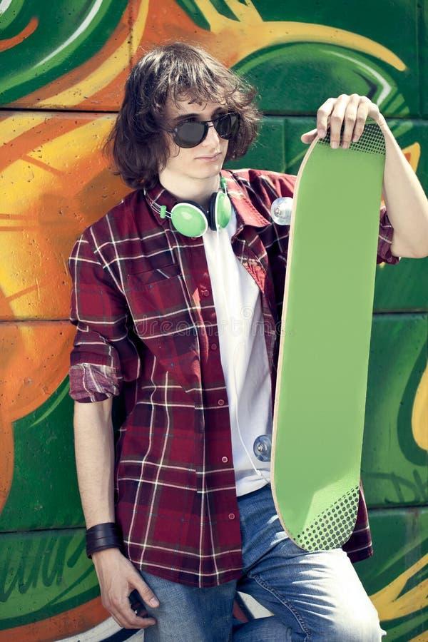 Koele schaatser tegen een graffitimuur royalty-vrije stock foto's