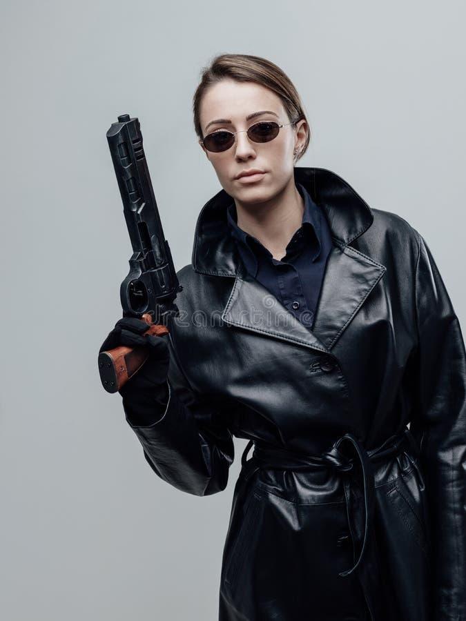 Koele vrouwelijke spion die een kanon houden royalty-vrije stock fotografie