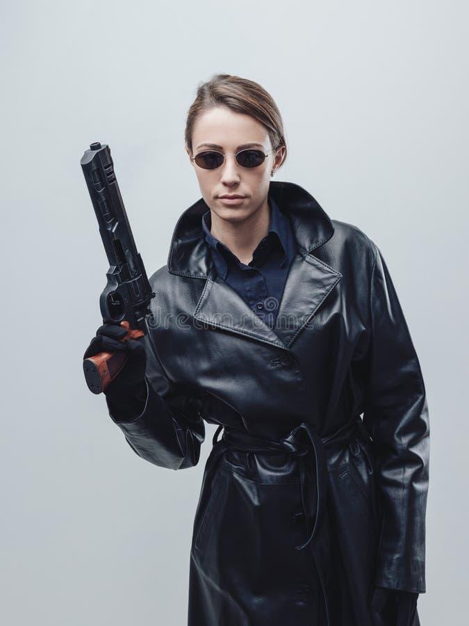 Koele vrouwelijke spion die een kanon houden stock afbeelding