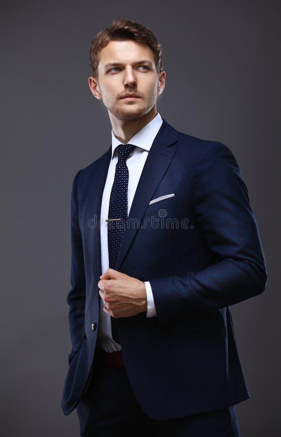 Koele zakenman die zich op grijs bevinden stock fotografie