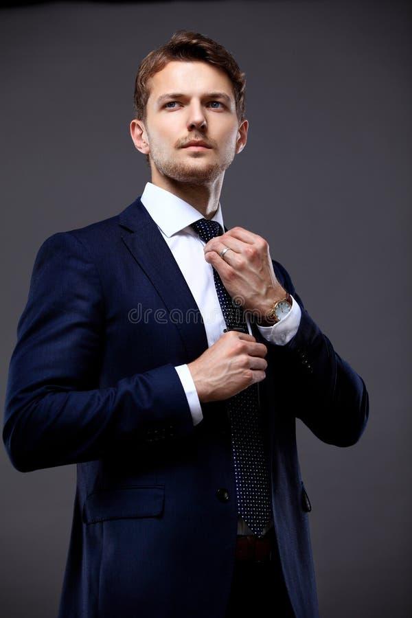 Koele zakenman die zich op grijs bevinden royalty-vrije stock afbeeldingen