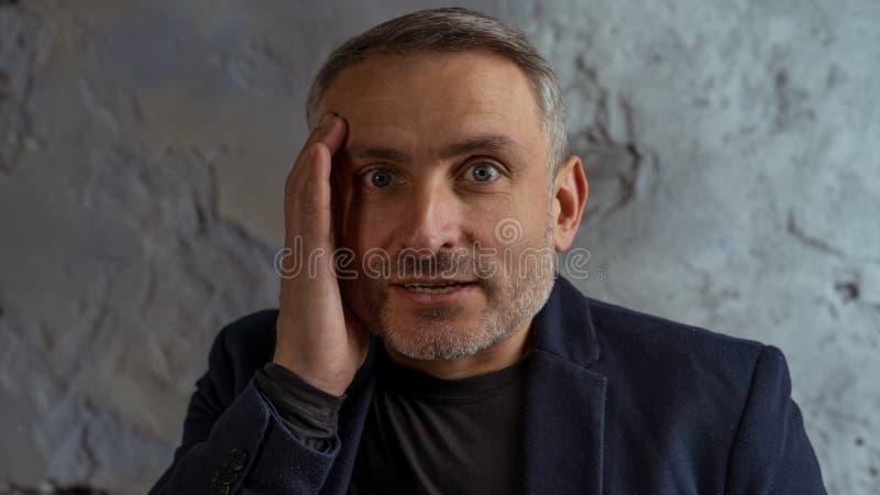 Koele zakenman met grijs haar en baard die zich op grijze achtergrond bevinden stock afbeelding