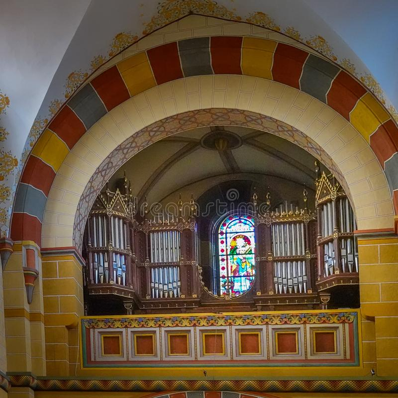 Pipes of the organ and a colorful window with a glass mosaic in the protestant cathedral. Koenigslutter, Germany, January 3., 2019: pipes of the organ and a stock photo