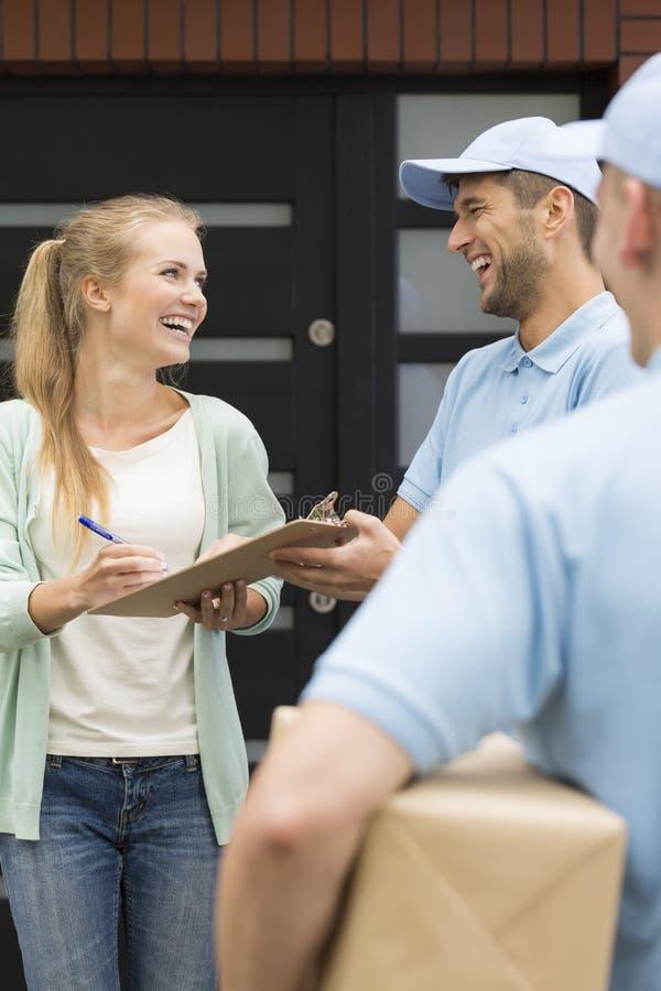 Koeriers die pakketten geven aan gelukkige klant die ontvangstbewijs ondertekenen stock afbeeldingen