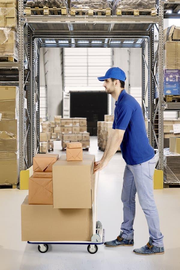 Koeriers duwende pakketten in het pakhuis stock afbeelding