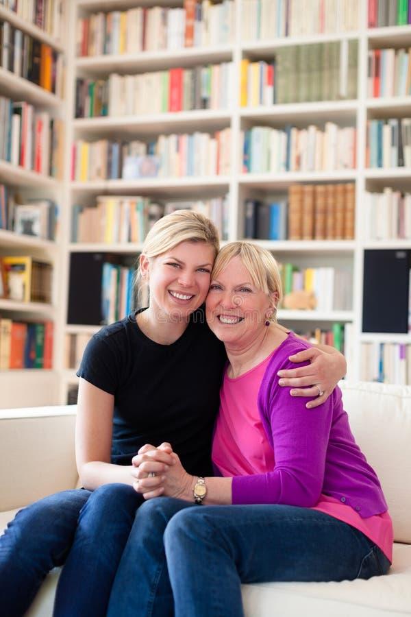 Koesteren van de moeder en van de dochter, die camera bekijkt royalty-vrije stock afbeelding