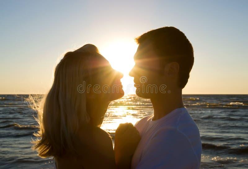 Koesteren van het paar, die de zomer van zonsondergang geniet. royalty-vrije stock foto's