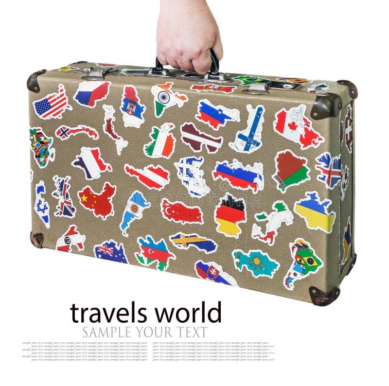 Koffer in der Hand mit Aufklebern von Flaggen von Ländern von der Reise lizenzfreie stockbilder