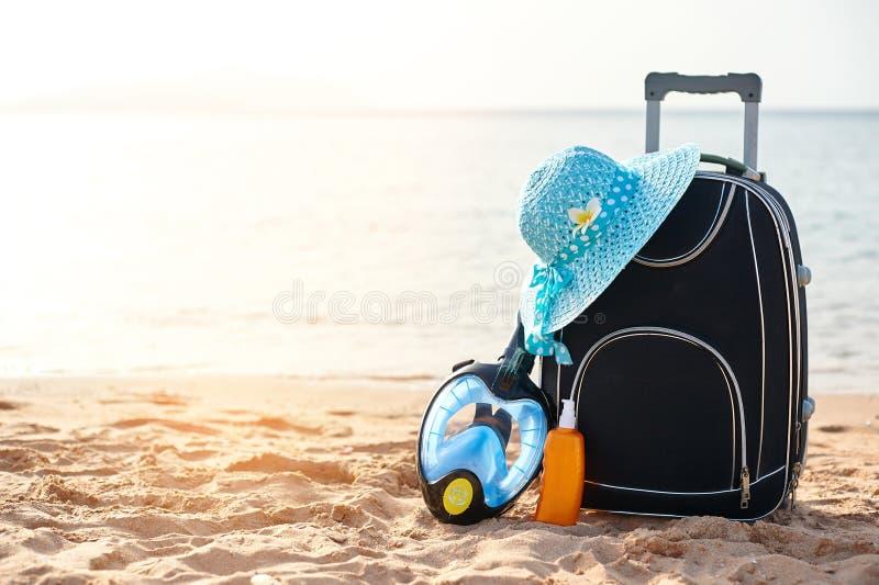 Koffer und Hut, Lichtschutz mit einer Maske Das tropische Meer, Strand im Hintergrund Das Konzept der Sommererholung stockbilder