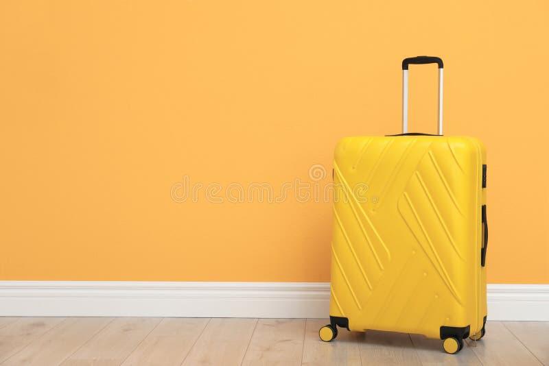 Koffer voor reis op vloer dichtbij kleurenmuur die wordt ingepakt royalty-vrije stock afbeeldingen