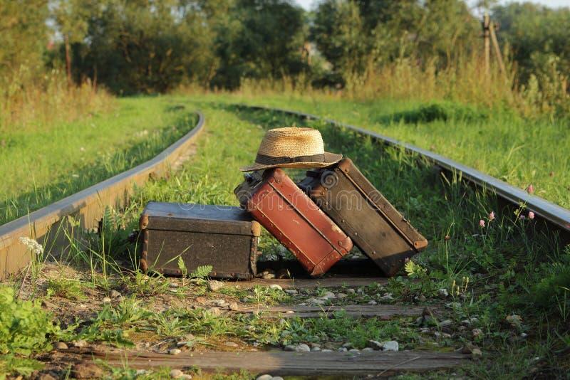 Koffers oude tribune op spoorwegtrackssuitcases oud op spoorwegsporen stock afbeeldingen