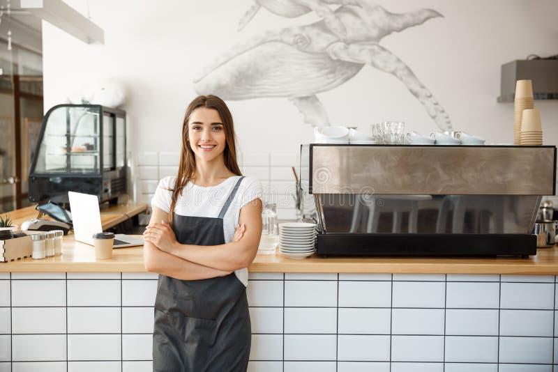 Koffie Bedrijfseigenaar Concept - Portret van gelukkige aantrekkelijke jonge mooie Kaukasische barista in schort die glimlachen b stock foto