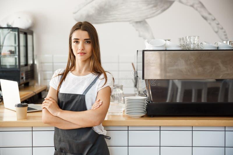 Koffie Bedrijfseigenaar Concept - Portret van gelukkige aantrekkelijke jonge mooie Kaukasische barista in schort met zeker royalty-vrije stock afbeeldingen