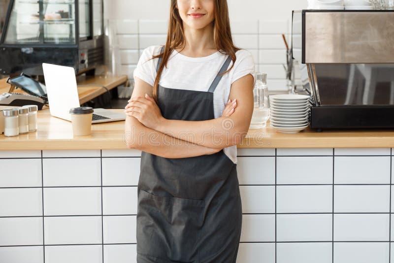 Koffie bedrijfseigenaarconcept - aantrekkelijke jonge mooie Kaukasische barista in schort die bij camera in koffiewinkel glimlach royalty-vrije stock foto
