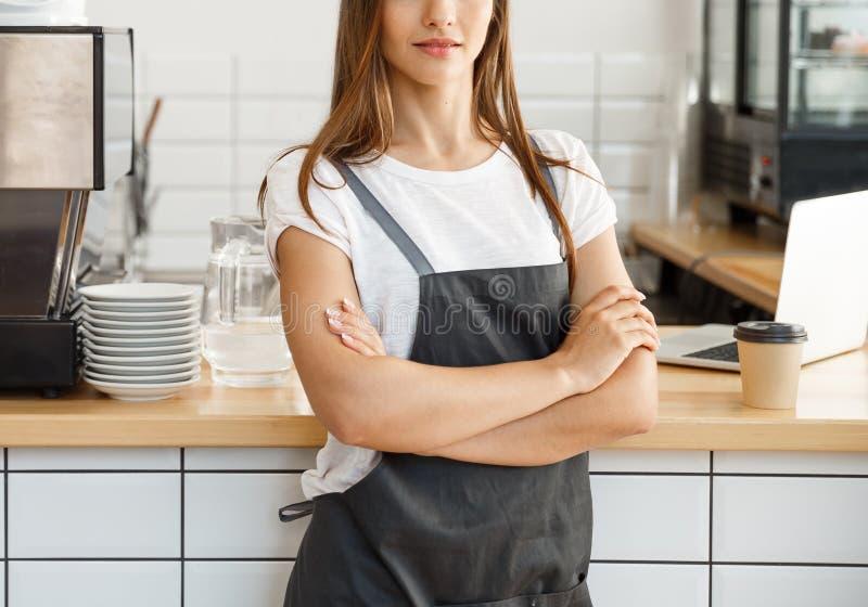 Koffie bedrijfseigenaarconcept - aantrekkelijke jonge mooie Kaukasische barista in schort met het zekere bekijken camera stock foto's