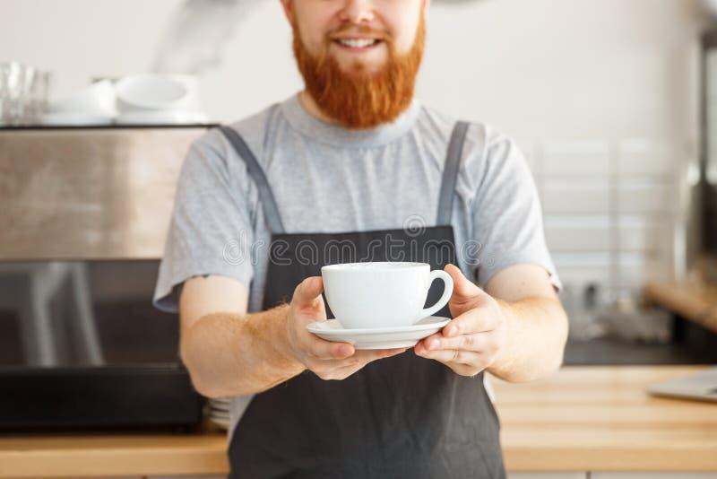 Koffie bedrijfseigenaarconcept - portret van gelukkige jonge gebaarde Kaukasische barista in schort met het zekere kijken royalty-vrije stock afbeeldingen