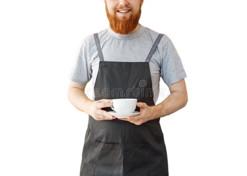 Koffie bedrijfseigenaarconcept - portret van gelukkige jonge gebaarde Kaukasische barista in schort met zekere lookin royalty-vrije stock foto's
