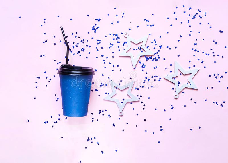 Koffie in beschikbare document koppen en witte sterren op roze pastelkleur in achtergrond royalty-vrije stock foto's