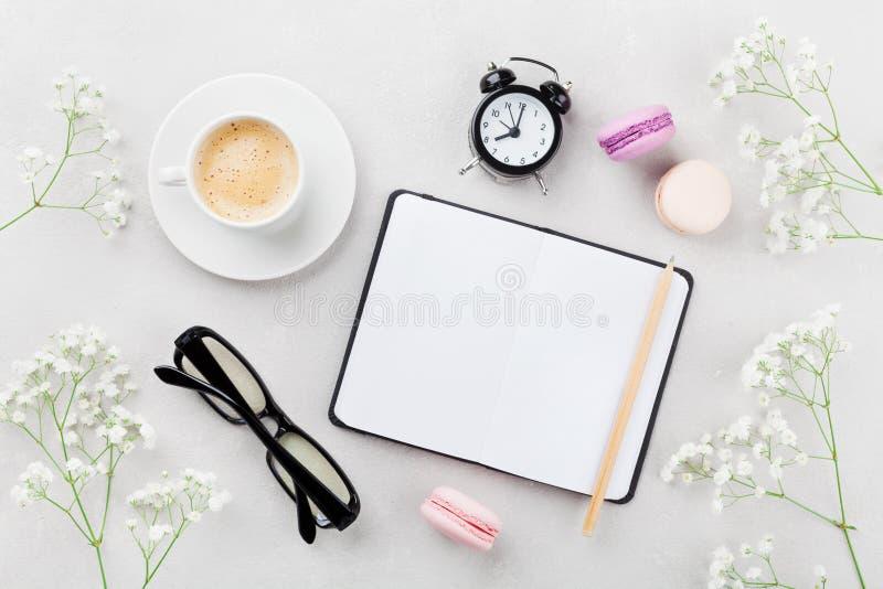 Koffie, cake macaron, notitieboekje, oogglazen, wekker en bloem voor ontbijt op de mening van de lijstbovenkant Vrouwen werkend b royalty-vrije stock afbeelding