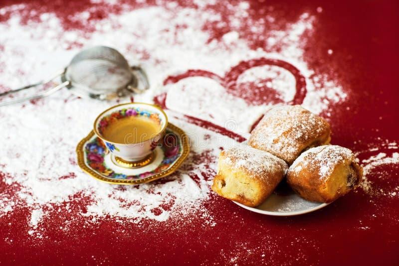 Koffie, cakes, zeefje en hart op rode achtergrond met bestrooide suiker royalty-vrije stock foto's