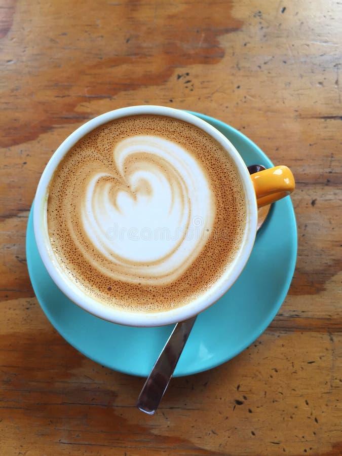 Koffie in een gele kop en een blauwe schotel stock foto's