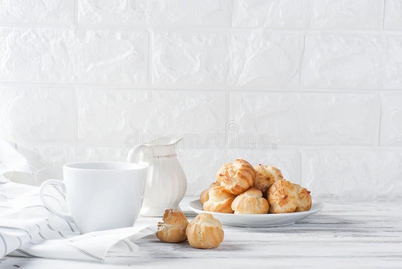Koffie en eclairs op een witte achtergrond royalty-vrije stock afbeeldingen