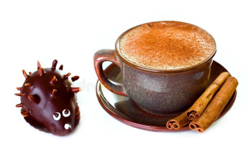 Koffie en kaneel met cake in de vorm van egel stock afbeelding