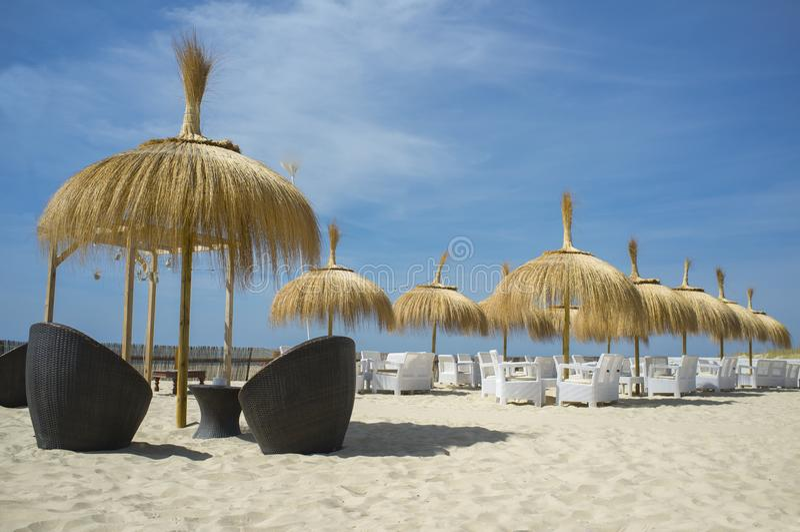 Koffie en restaurantleunstoelen met lijst en paraplu bij strand stock foto's
