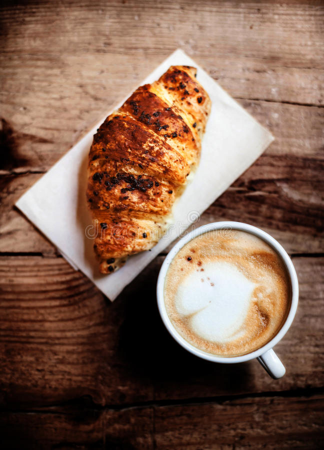 Koffie en vers croissant voor ontbijt op rustieke houten lijst, stock afbeeldingen