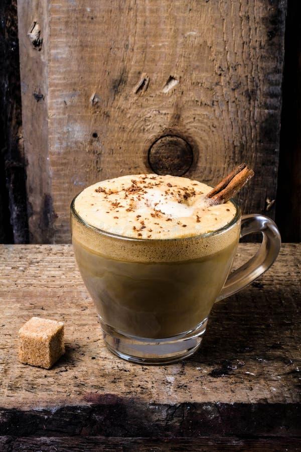 Koffie in glaskop met room, kaneel en bestrooid chocolat stock foto
