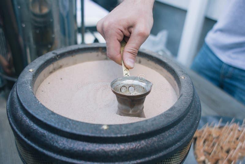 Koffie in het voorbereidingen treffen van Turk op heet zand - Straatvoedsel stock fotografie