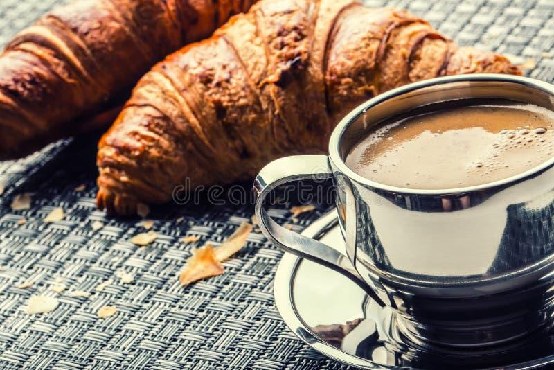 Koffie Kop van koffie Roestvrij staalkop koffie en twee croissants Koffiepauze bedrijfsonderbreking stock foto