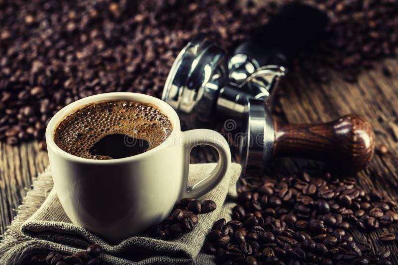 Koffie Kop van zwarte coffe met de stamper van koffiebonen en portafilter stock fotografie