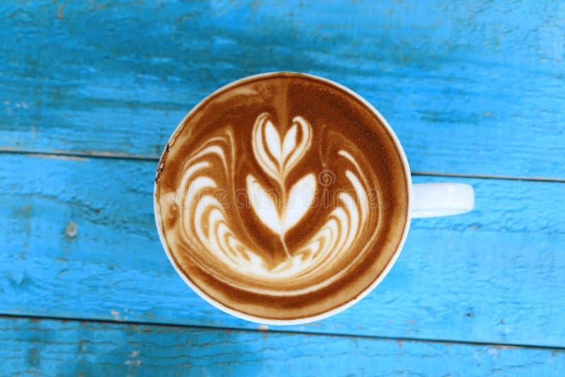 Koffie latte kunst met patroon de bladeren in koppen op blauwe woode royalty-vrije stock afbeeldingen