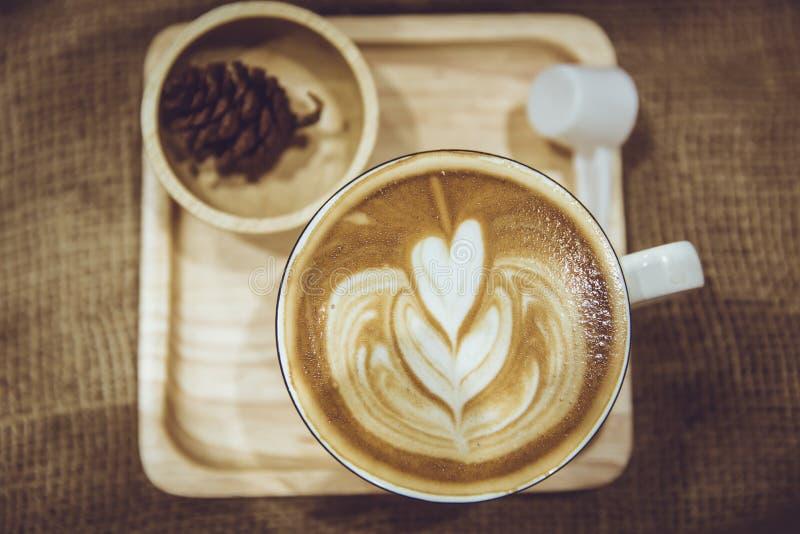 Koffie latte kunst op houten die plaat wordt in koffie wordt verfraaid gediend die royalty-vrije stock afbeeldingen