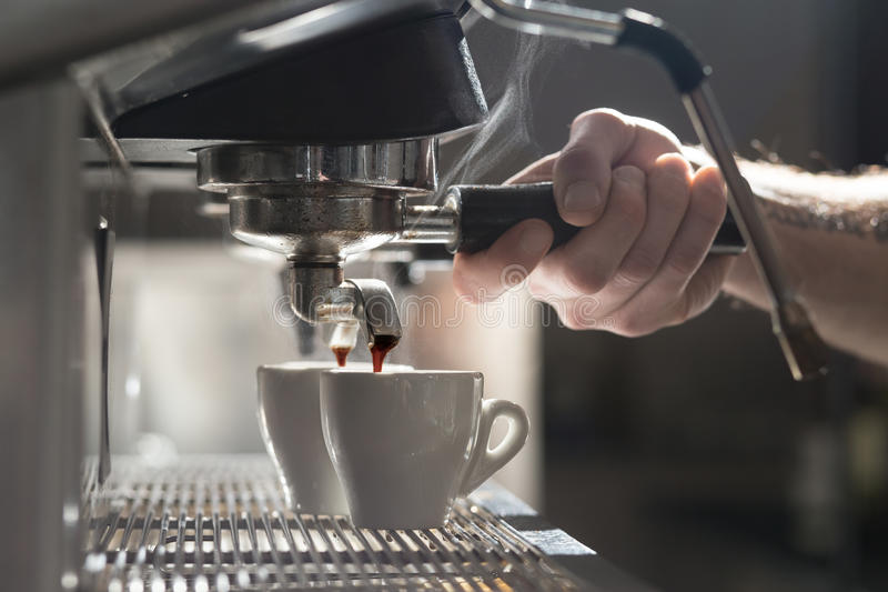 Koffie makend proces; espressokop en koffiemachine; stock foto