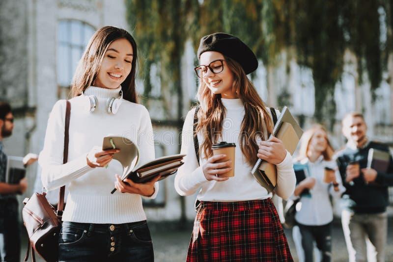 Koffie meisjes gelukkig samen student binnenplaats stock afbeelding