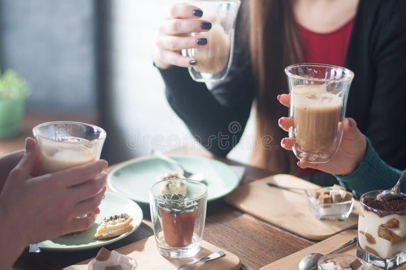 Koffie, melk, kop, heerlijke handen, dessert, comfortabele koffie, zonnige dag, rode spijkers, vrienden, pretbedrijf, mededeling stock foto