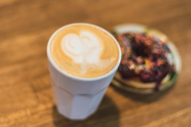 Koffie met een hart van melk wordt gemaakt en een doughnut op een houten lijst die Koffie met een getrokken hart en melk op een h royalty-vrije stock afbeeldingen