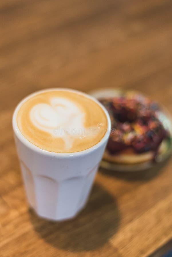 Koffie met een hart van melk wordt gemaakt en een doughnut op een houten lijst die Koffie met een getrokken hart en melk op een h royalty-vrije stock afbeelding
