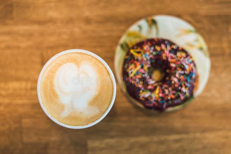 Koffie met een hart van melk wordt gemaakt en een doughnut op een houten lijst die Koffie met een getrokken hart en melk op een h stock fotografie