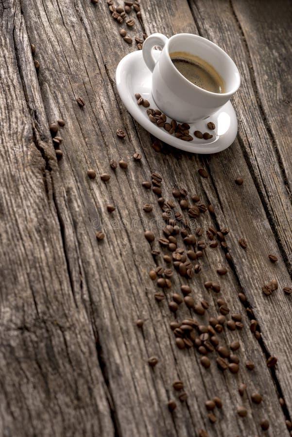 Koffie met gemorste bonen op houten lijst stock foto's