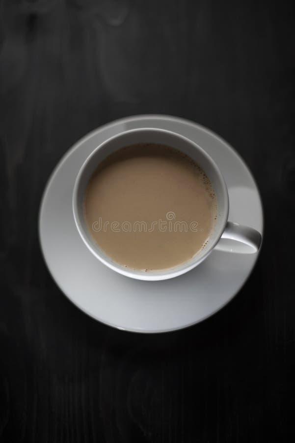Koffie met melk in een witte kop en schotel op een zwarte houten lijst, onderbreking voor hete dranken hoogste mening royalty-vrije stock foto's